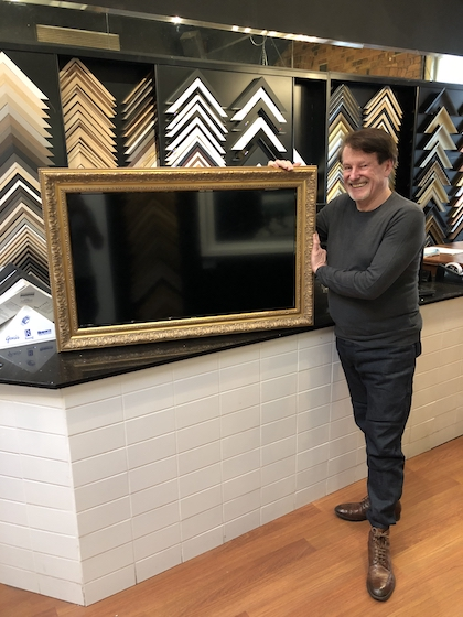 Greg Mahoney with a television framed in a gold ornate frame.