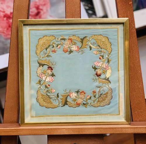 A fabric framed in a gold water gilded Bellini timber frame with glass.